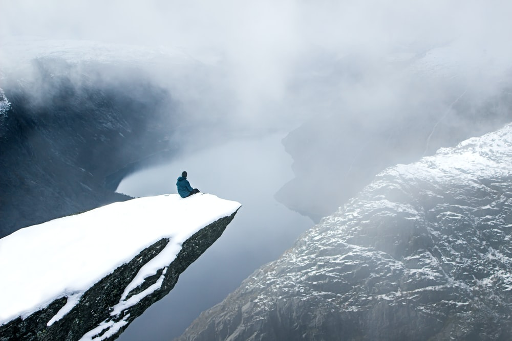 person in blue jacket and black pants standing on snow covered mountain during daytime