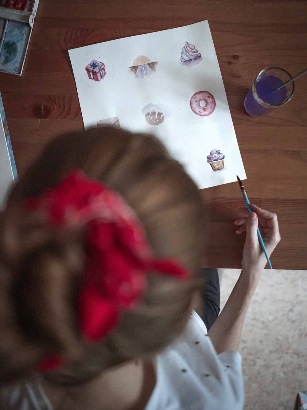 girl in white shirt holding pink and blue paint brush