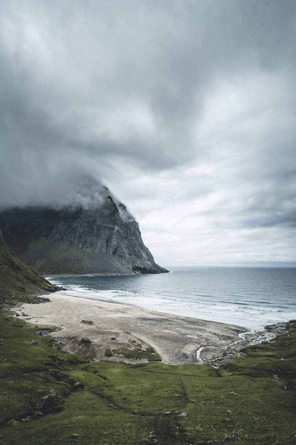 green and gray mountain beside body of water under cloudy sky during daytime