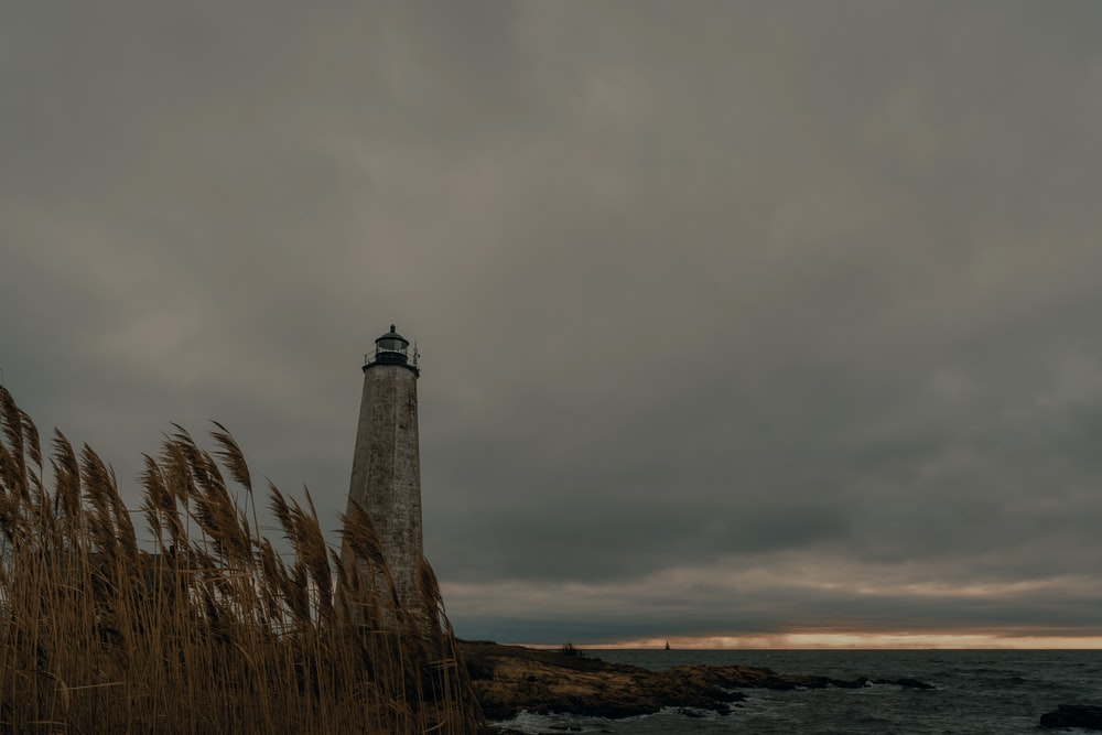 white and brown lighthouse near body of water under gray clouds
