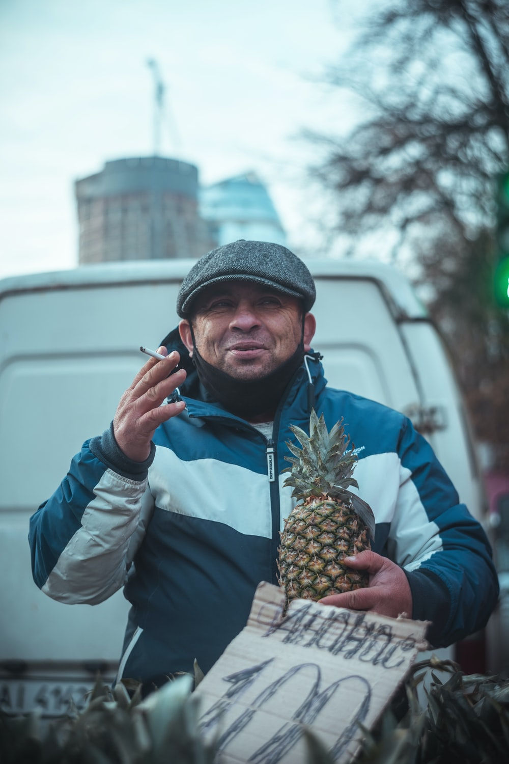 man in blue jacket and gray knit cap holding pineapple fruit