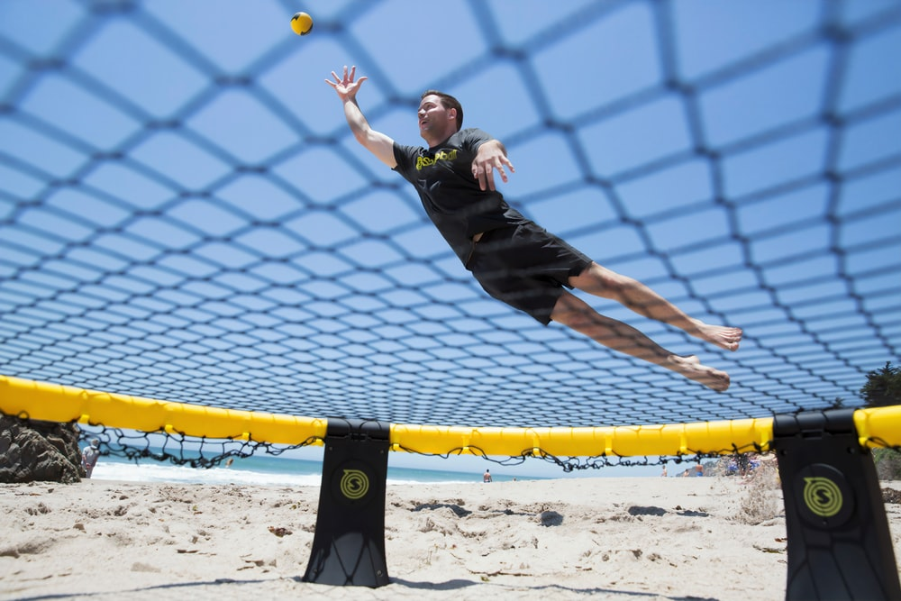 girl in black shirt and black pants jumping on yellow and blue net