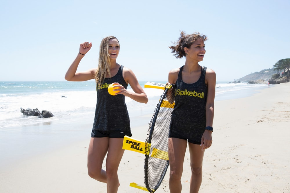 2 women holding yellow and black tennis racket on beach during daytime