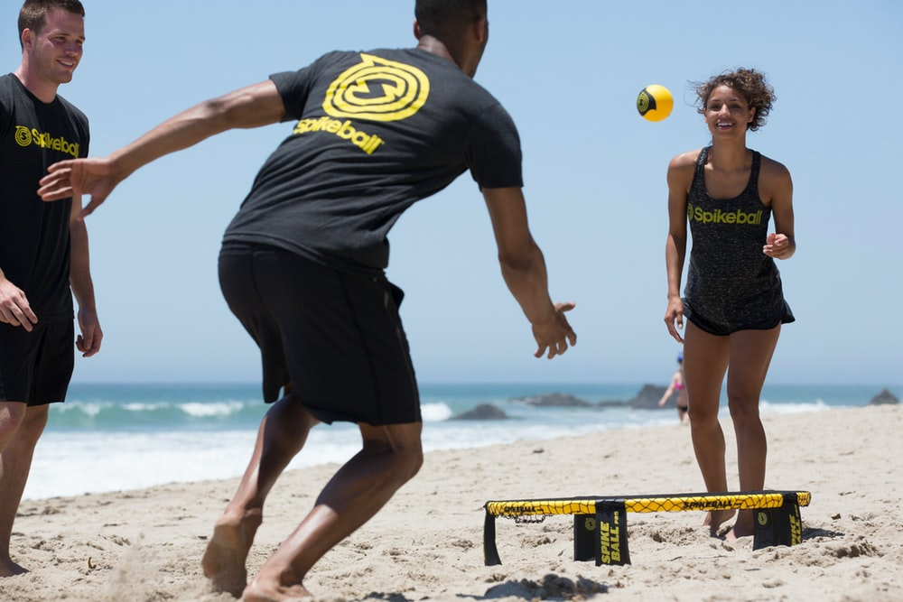 man in black and yellow nike crew neck t-shirt and black shorts standing on beach