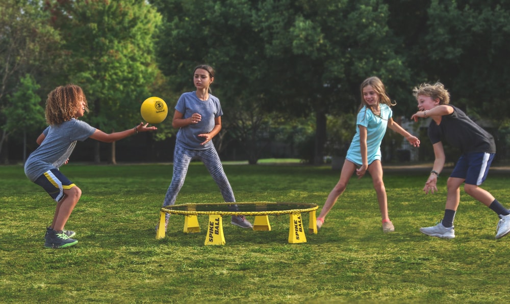 2 women playing soccer on green grass field during daytime