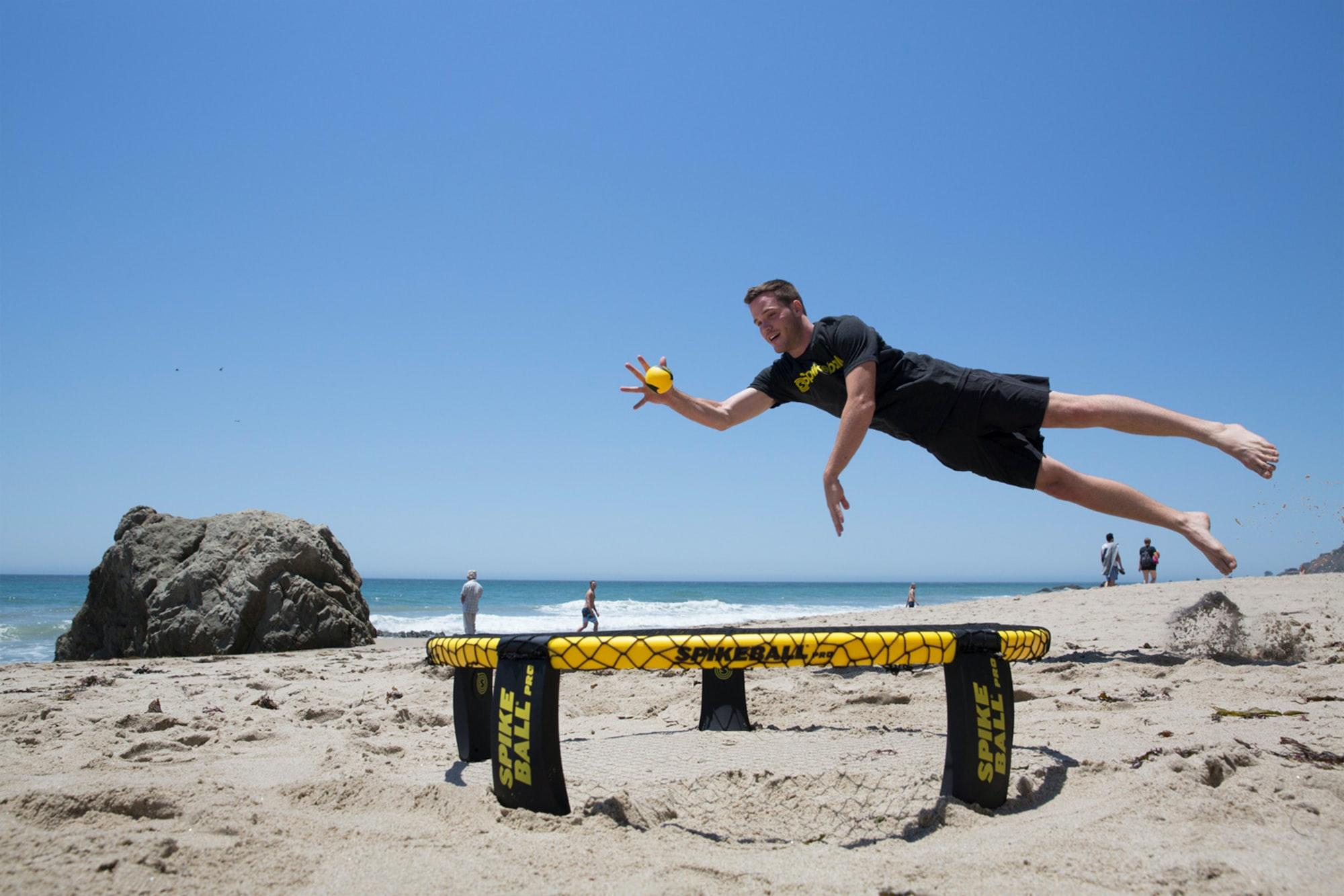 Guy diving for ball over Spikeball net on the beach