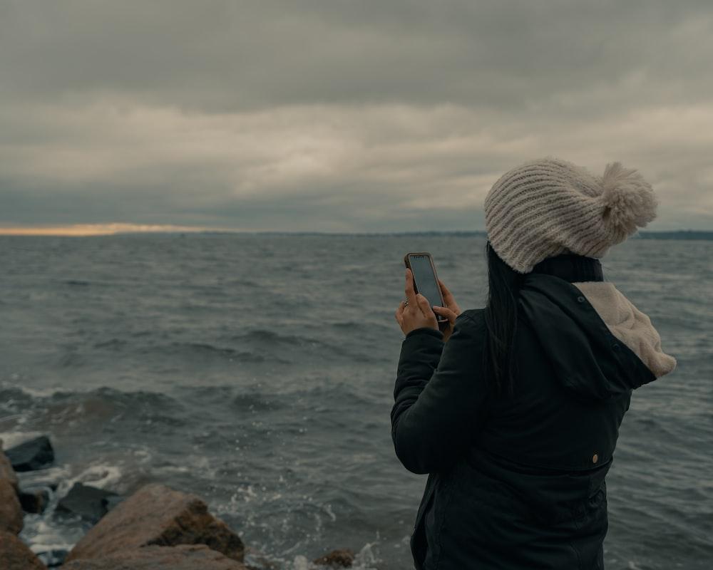 man in black jacket taking photo of sea during daytime