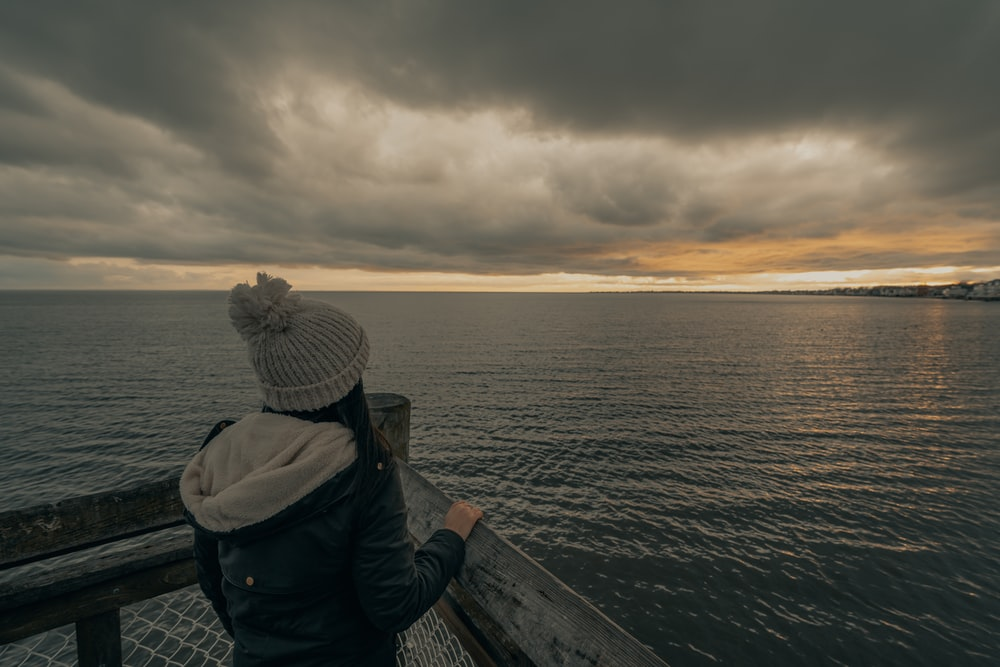 person in black jacket standing on wooden dock during daytime