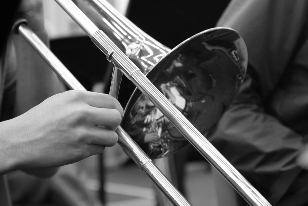 person playing trumpet in grayscale photography