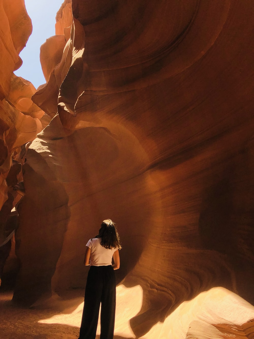 woman in white shirt and black pants standing in front of brown rock formation during daytime