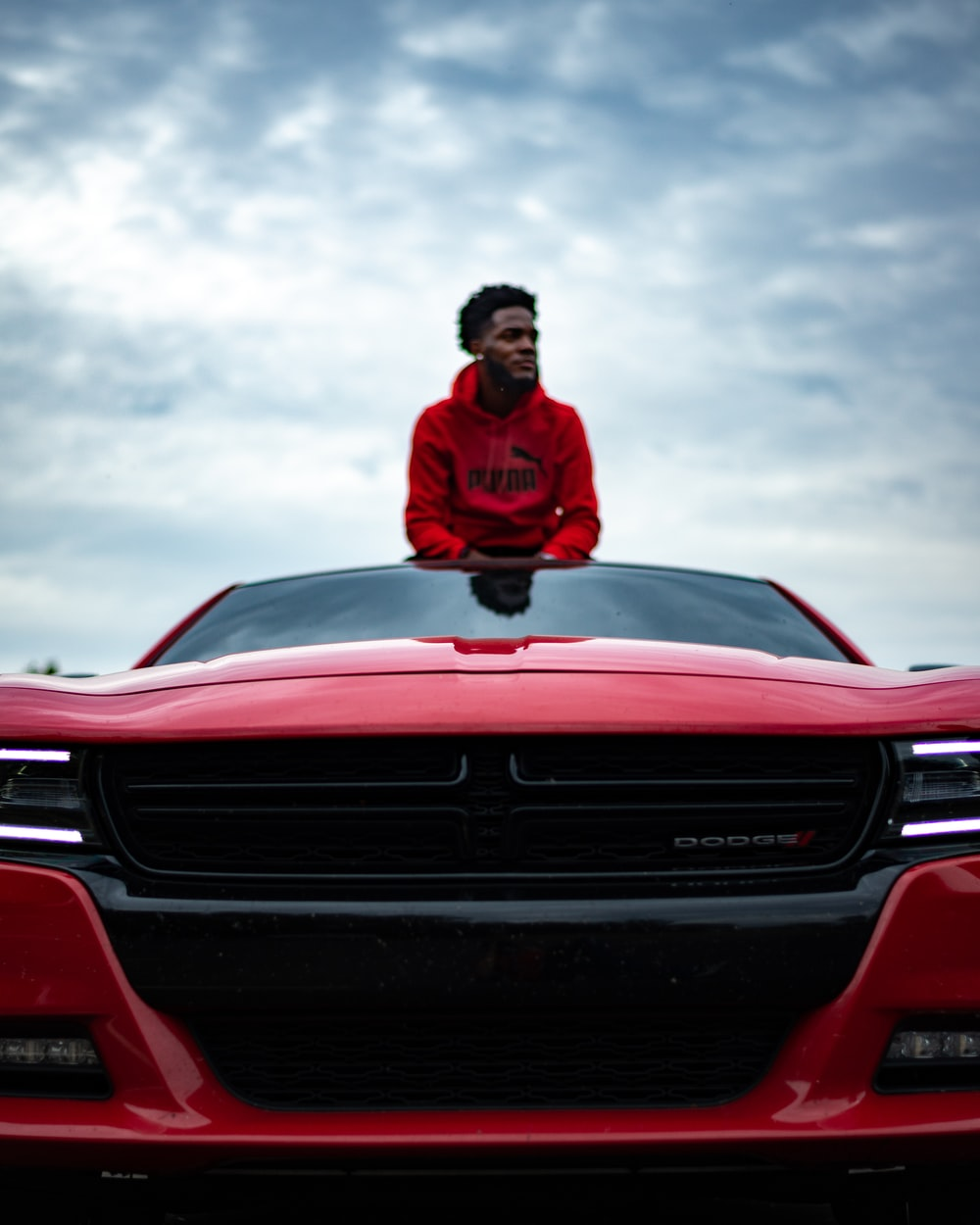 man in red jacket sitting on red chevrolet car