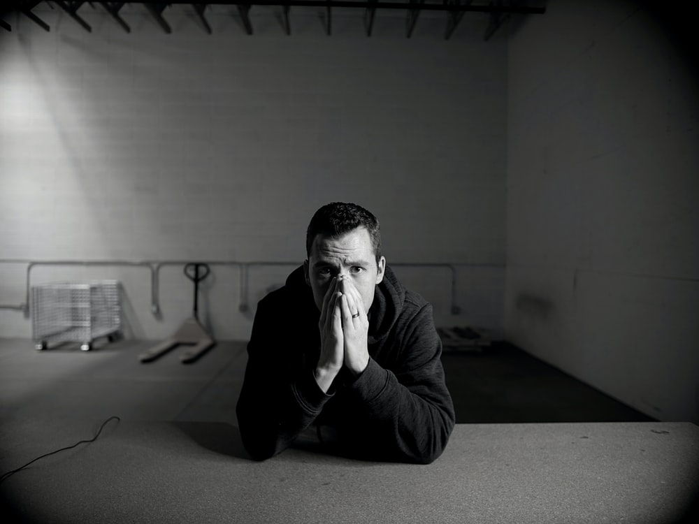 man in black jacket sitting on floor
