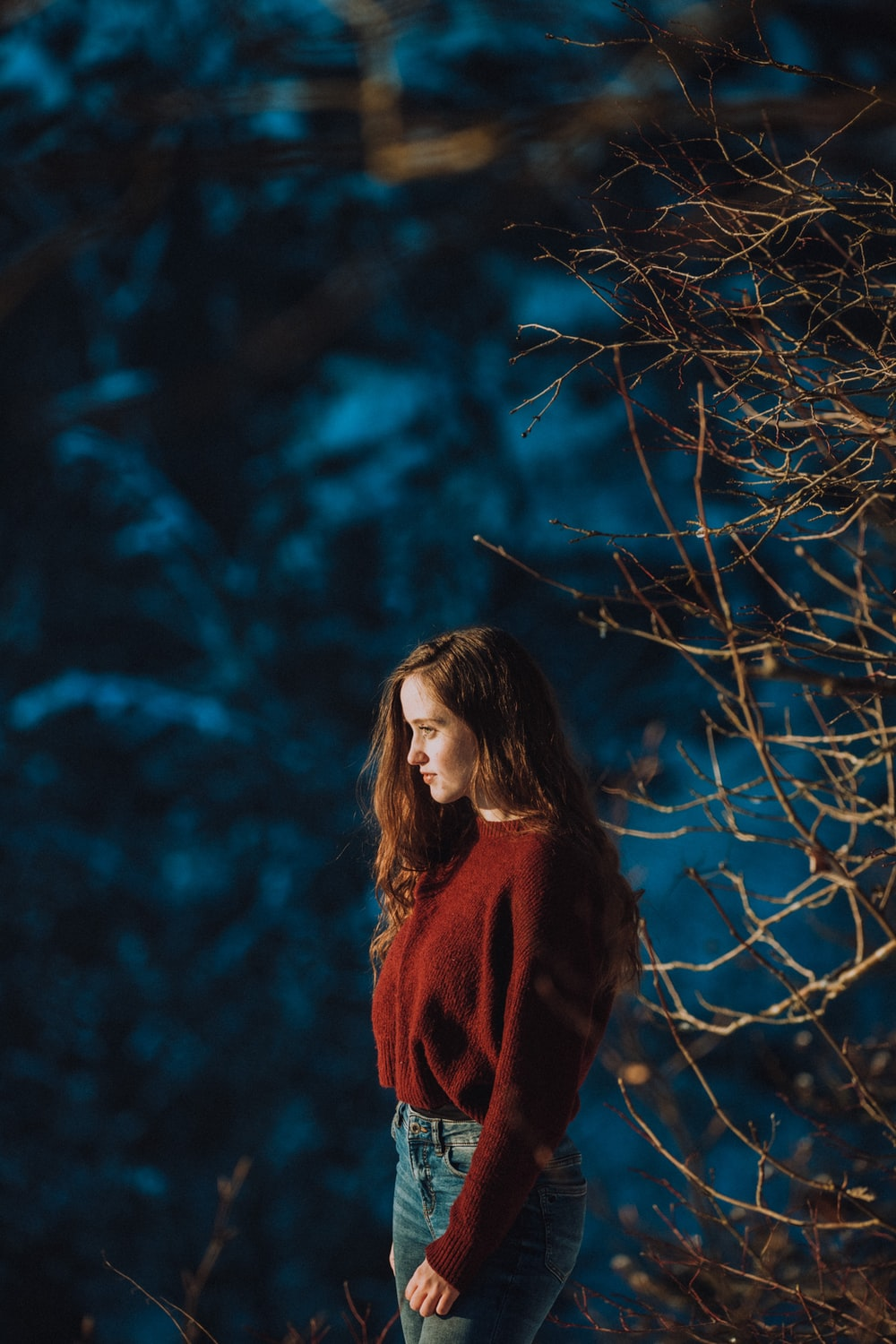 woman in red and black scarf standing near bare tree
