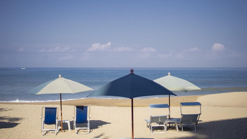 blue and white patio umbrella on beach during daytime