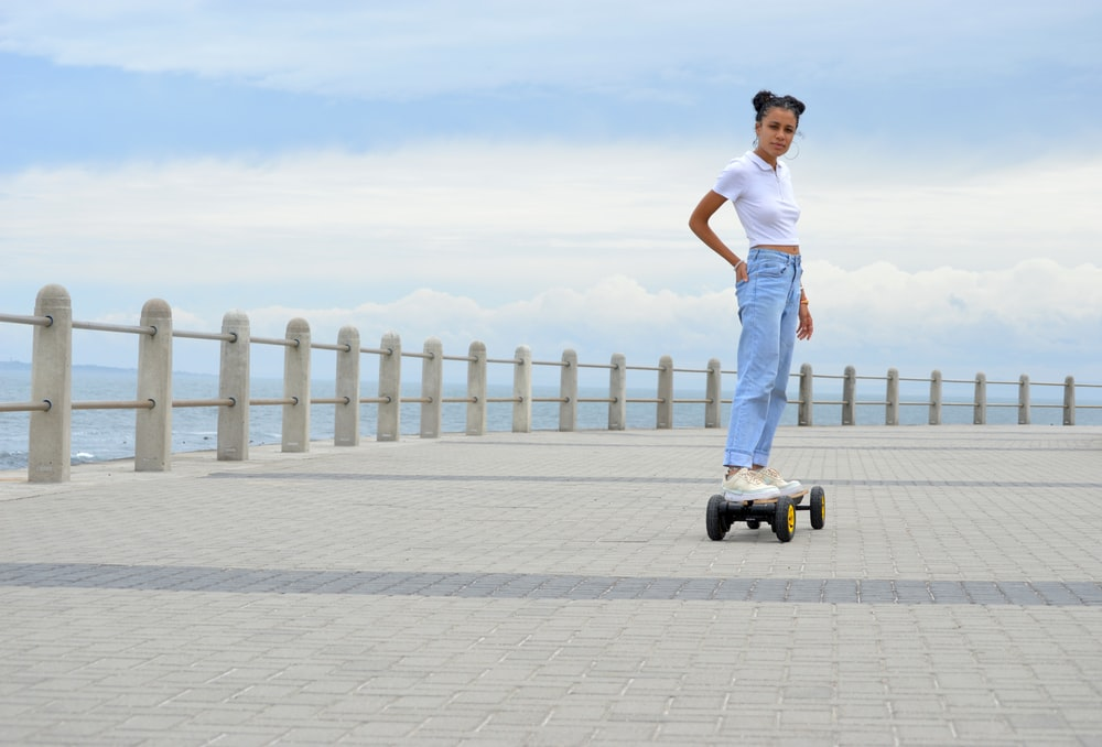 man in white tank top and blue denim jeans standing on gray concrete floor during daytime