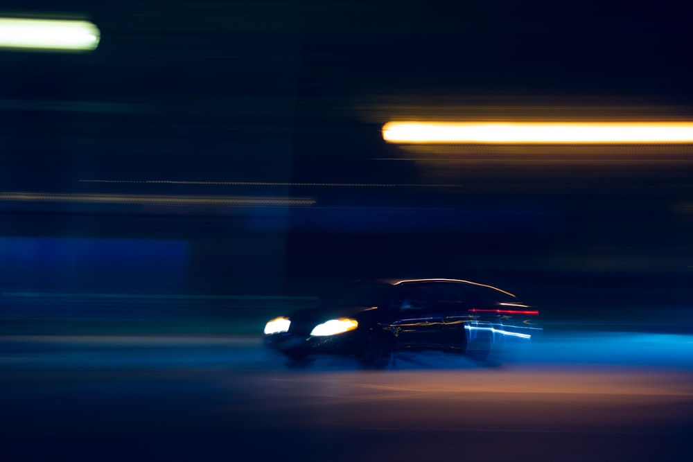 black car on road during night time