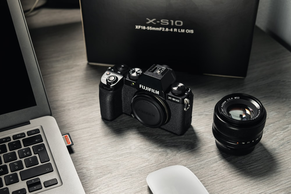 black nikon dslr camera beside white computer keyboard