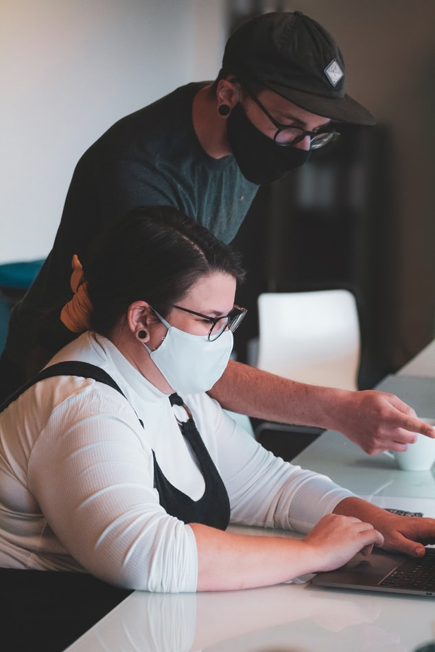 Two co-workers with masks on collaborating