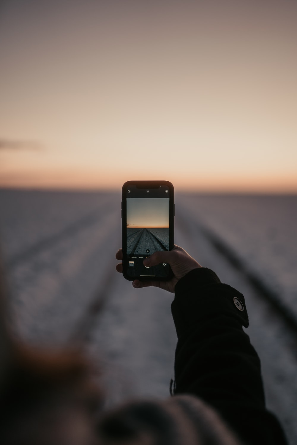 person holding iphone taking photo of sun