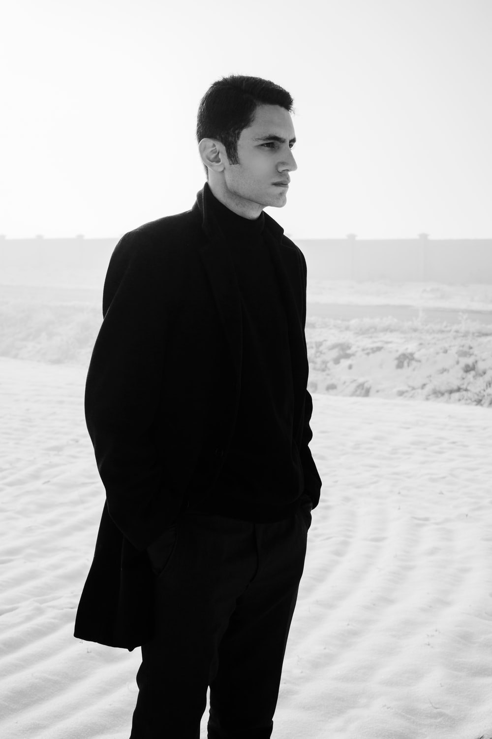 man in black coat standing on sand during daytime