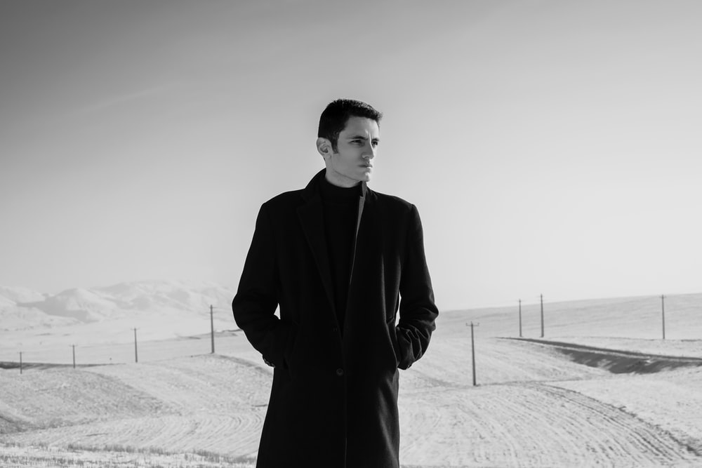 man in black coat standing on snow covered ground