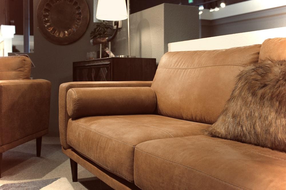 brown sofa near black round wall clock
