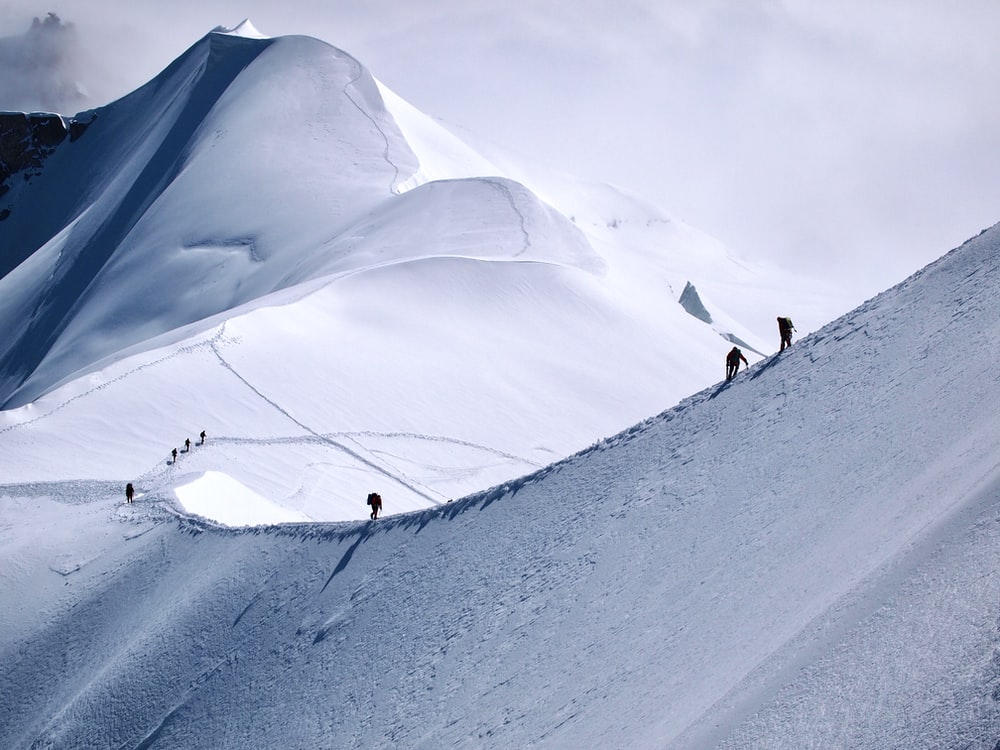 people walking on snow covered mountain during daytime