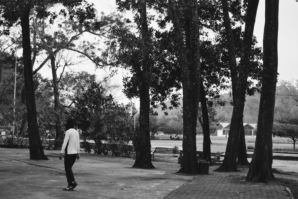 man in white dress shirt and black pants walking on park