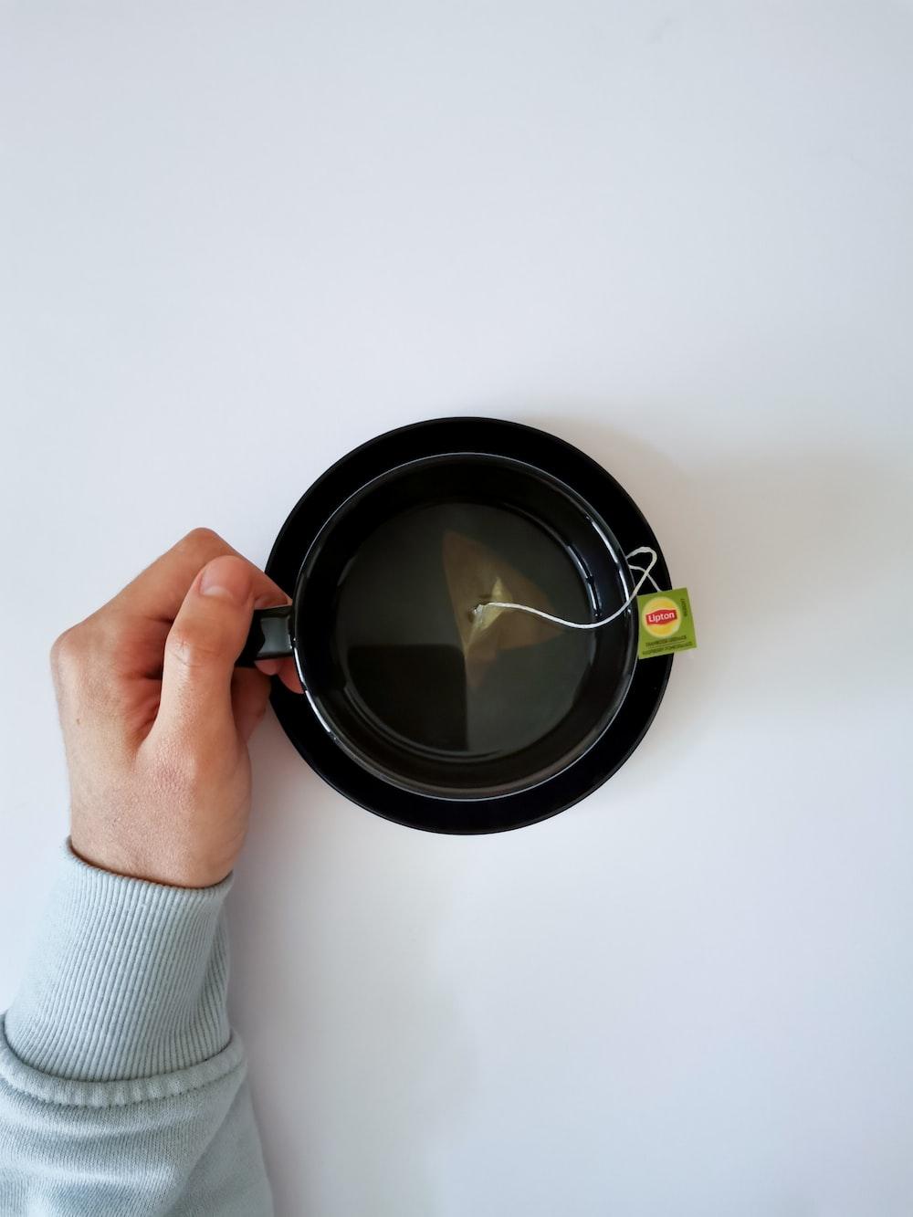 person holding black ceramic mug with black liquid