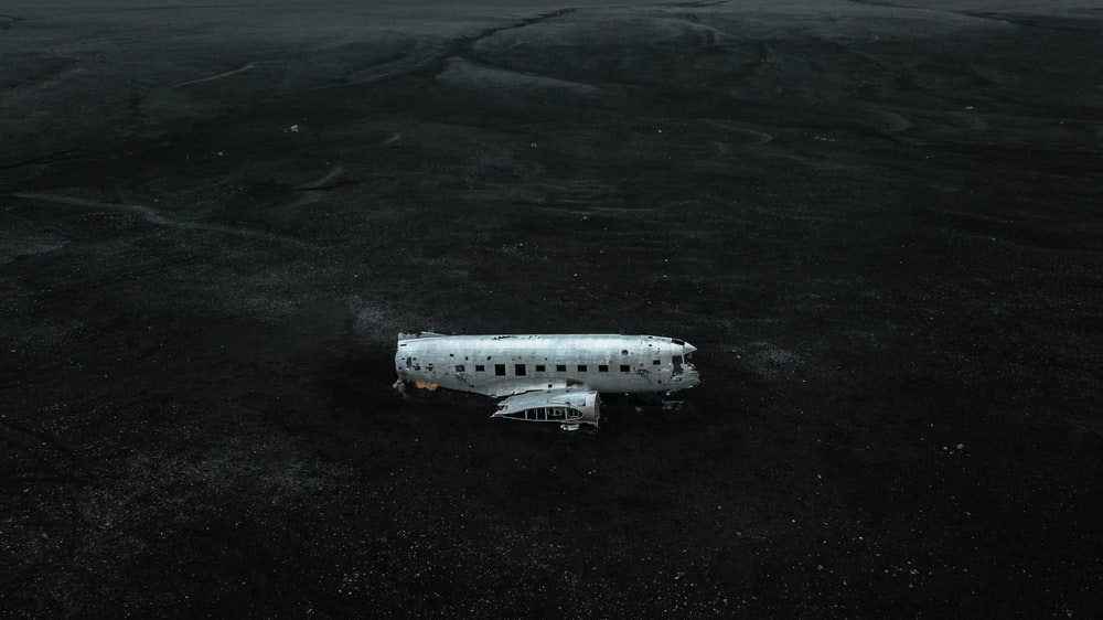 white and black airplane on black sand
