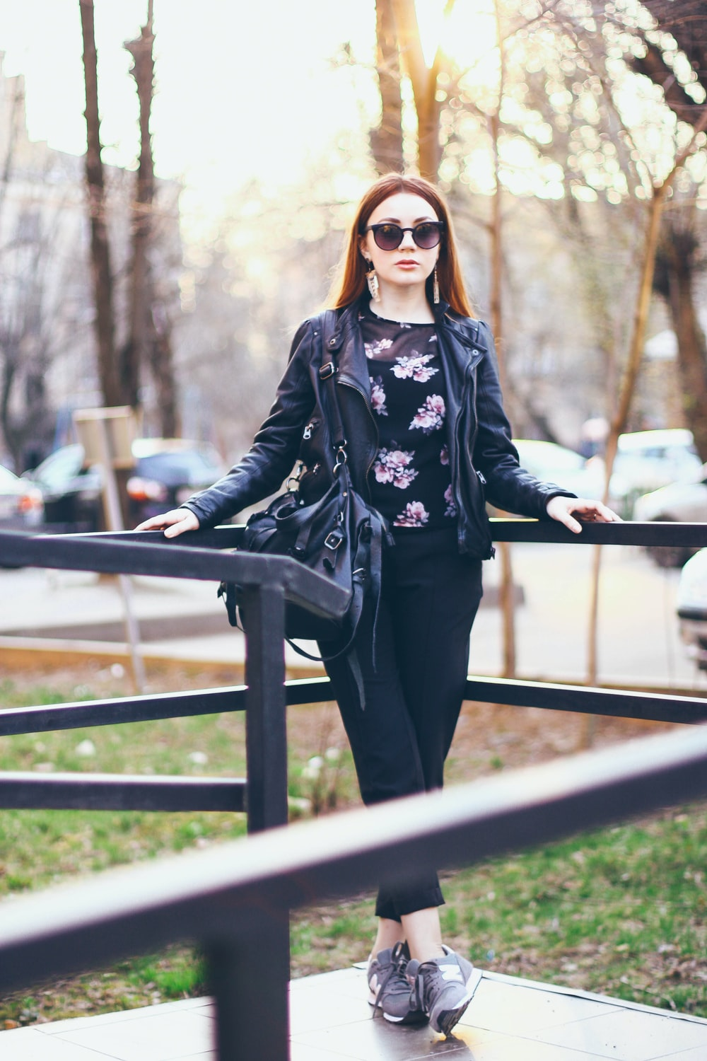 woman in black and white floral long sleeve shirt and black pants wearing sunglasses