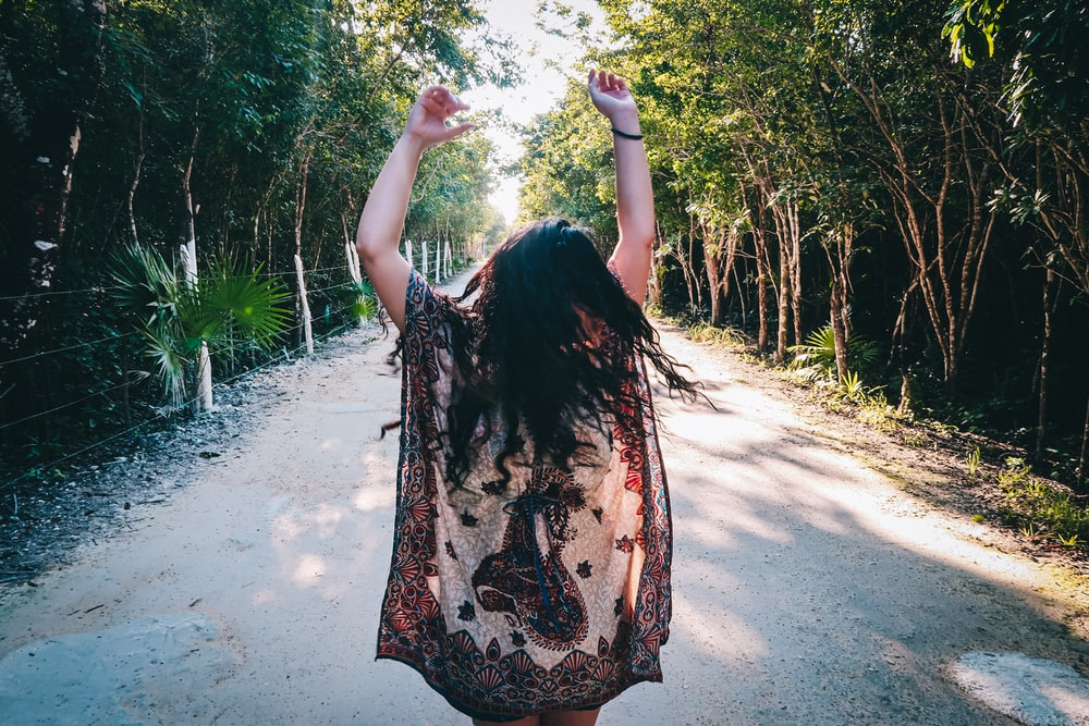 woman in black and brown floral dress standing on dirt road during daytime