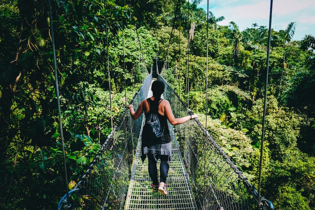 woman walks across a canopy bridge in Costa Rica, Pura Vida