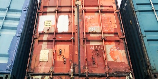 Stacks of containers at a port, with trucks in the background.