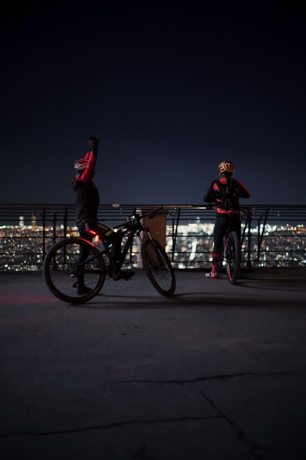 man in red hoodie and red pants riding on bicycle during night time