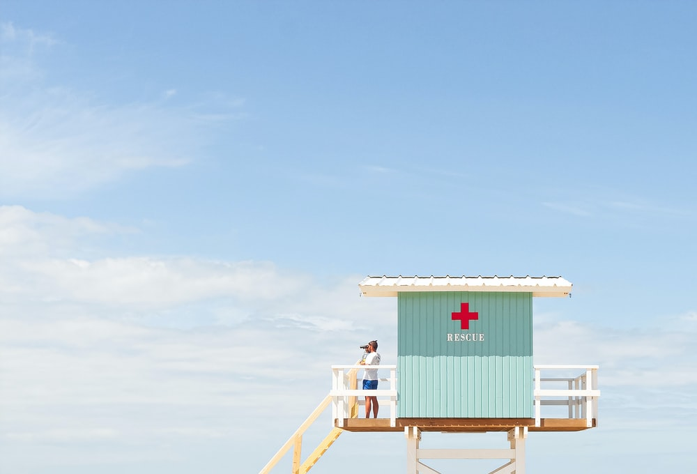 white and red wooden lifeguard house under blue sky during daytime