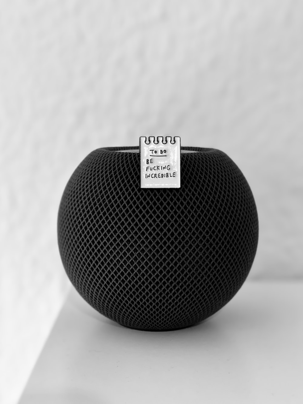 black round portable speaker on white table