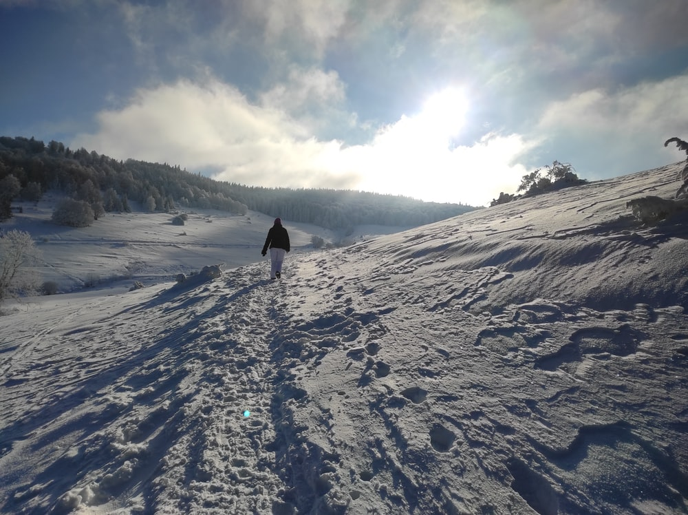person walking on snow covered mountain during daytime