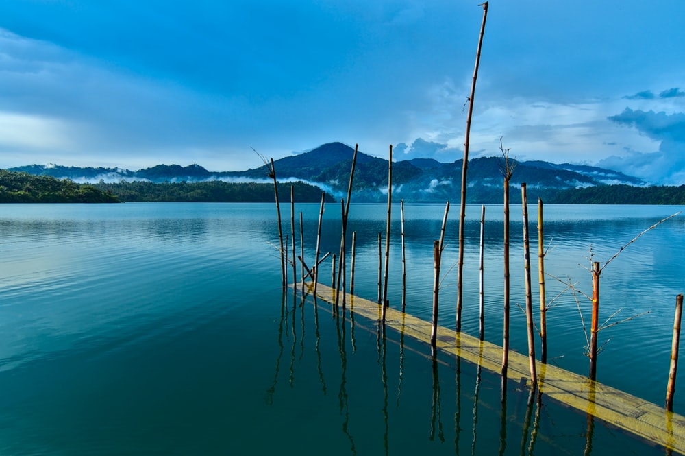 brown wooden dock on calm sea under blue sky during daytime