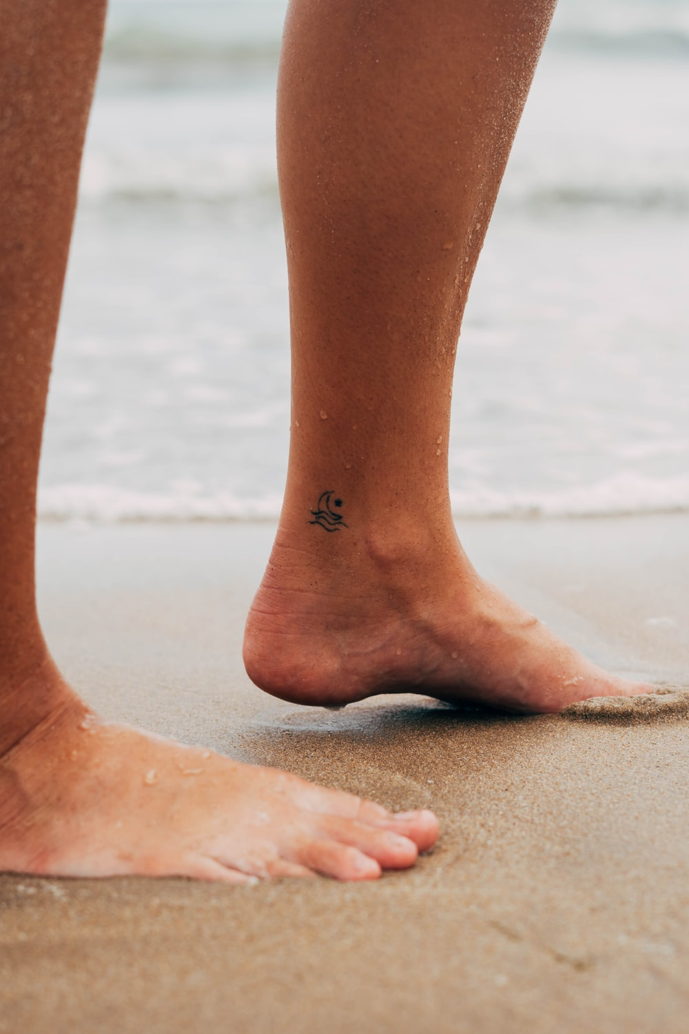 persons feet on white sand during daytime