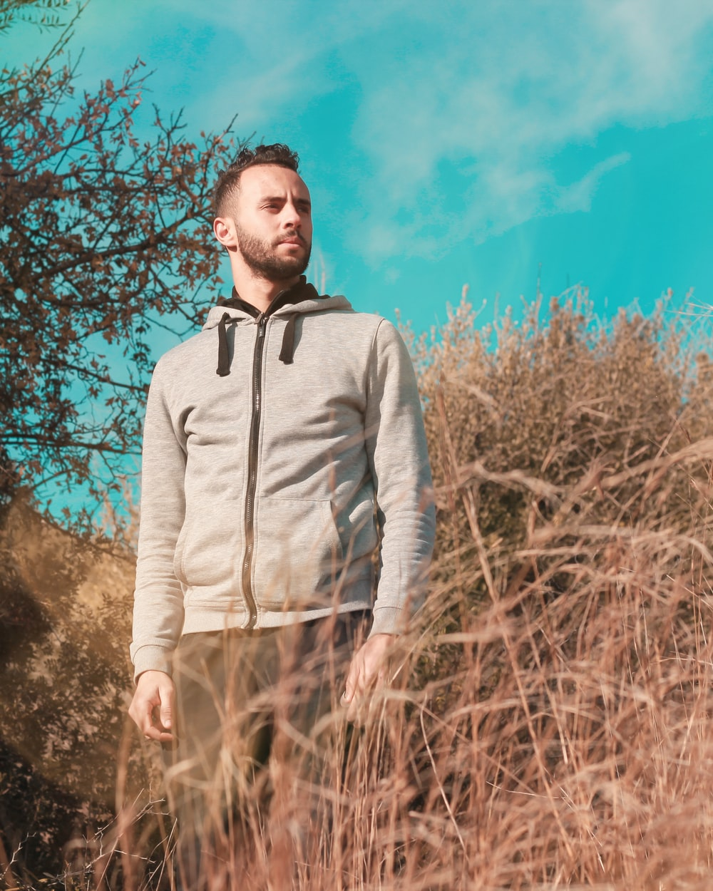 man in gray zip up jacket standing on brown grass field during daytime