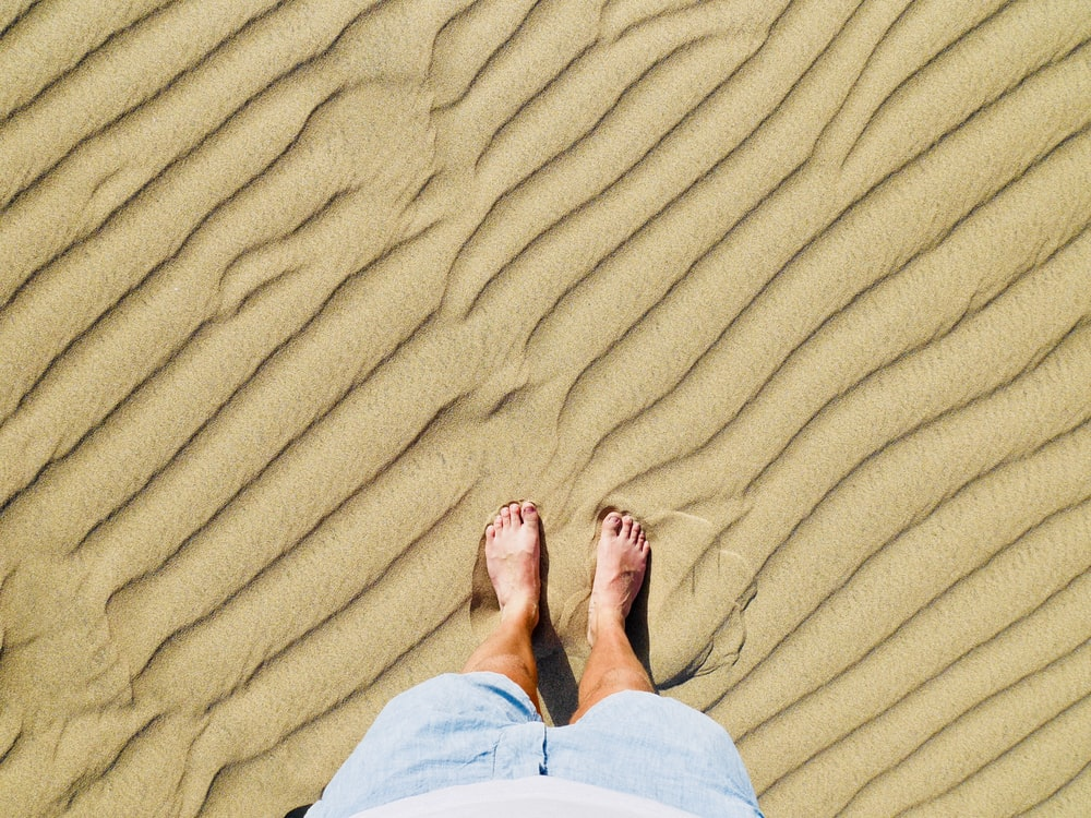 person in white pants standing on brown sand