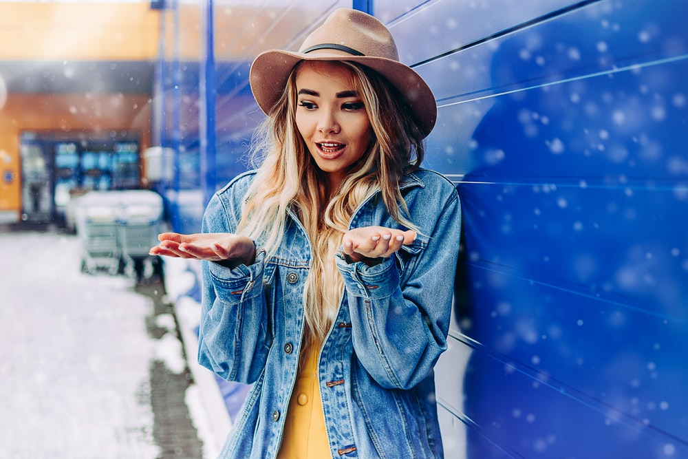 woman in blue denim jacket and brown fedora hat