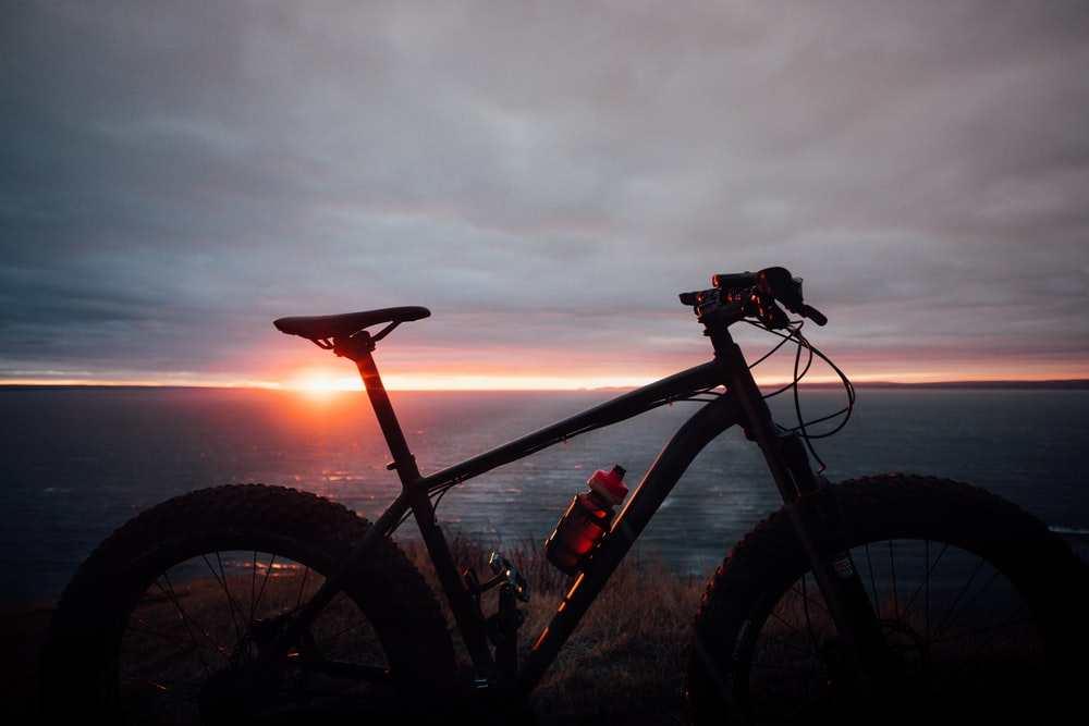 black and red hardtail mountain bike near body of water during sunset