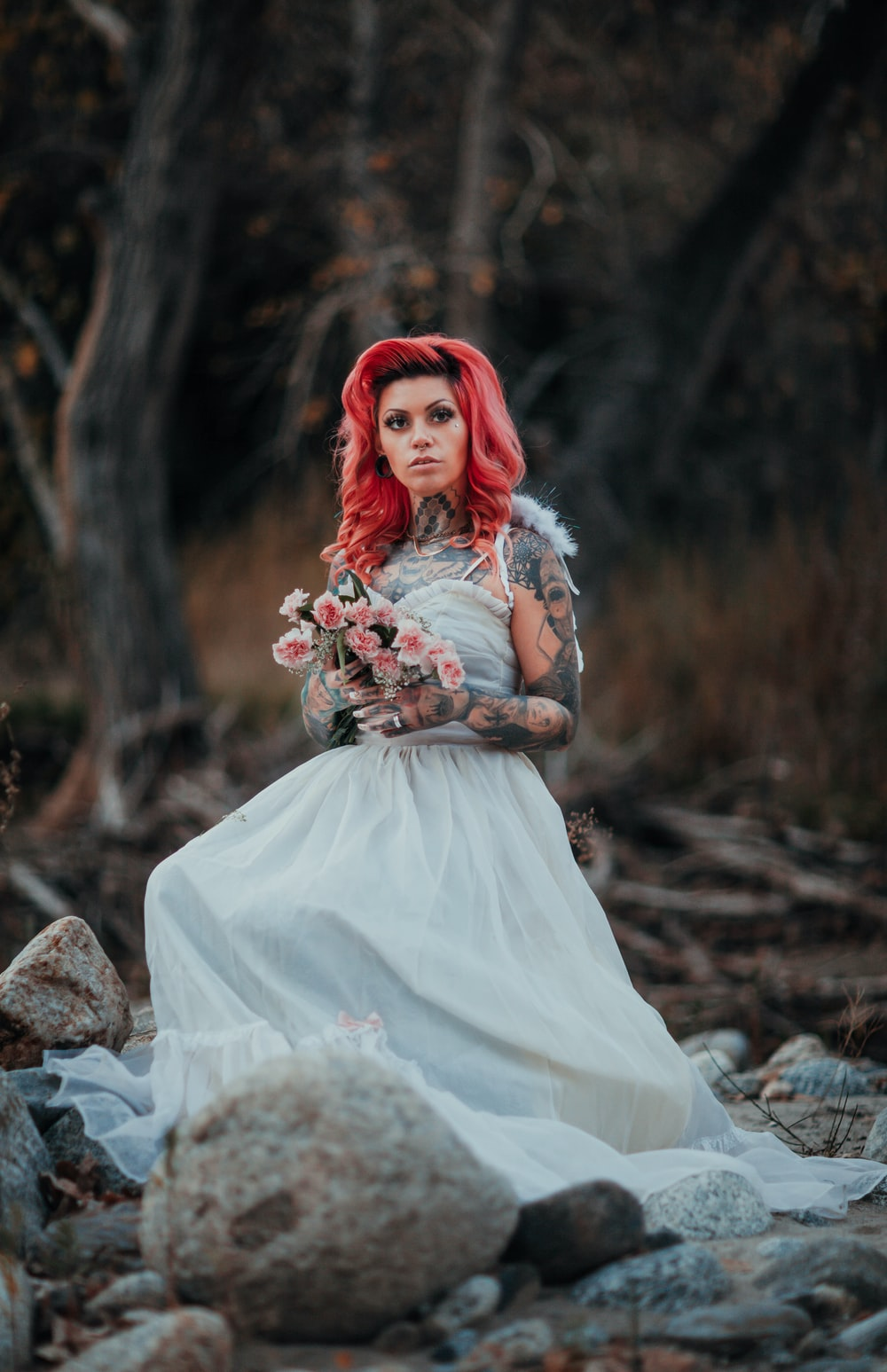 woman in white dress sitting on rock