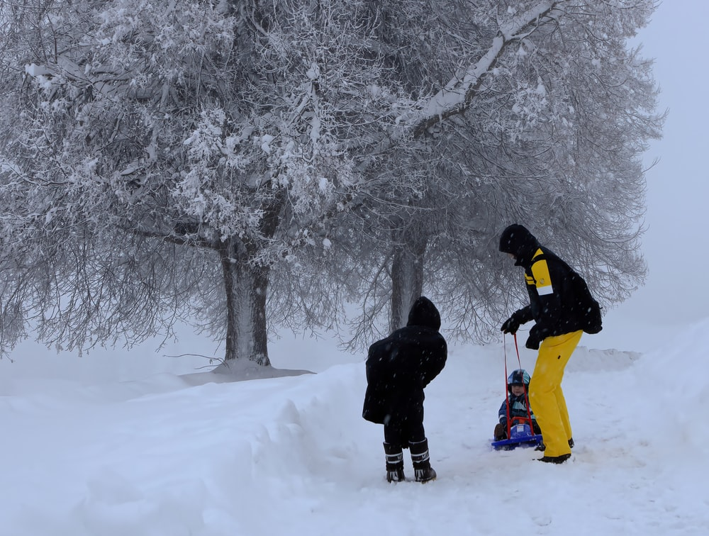 man in black jacket and yellow pants standing on snow covered ground during daytime