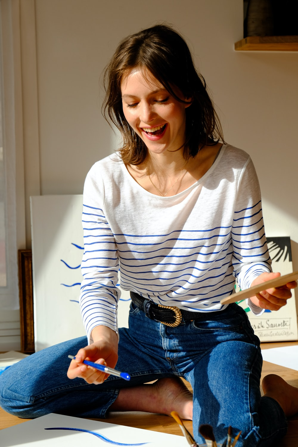 woman in white and black striped long sleeve shirt and blue denim jeans sitting on bed