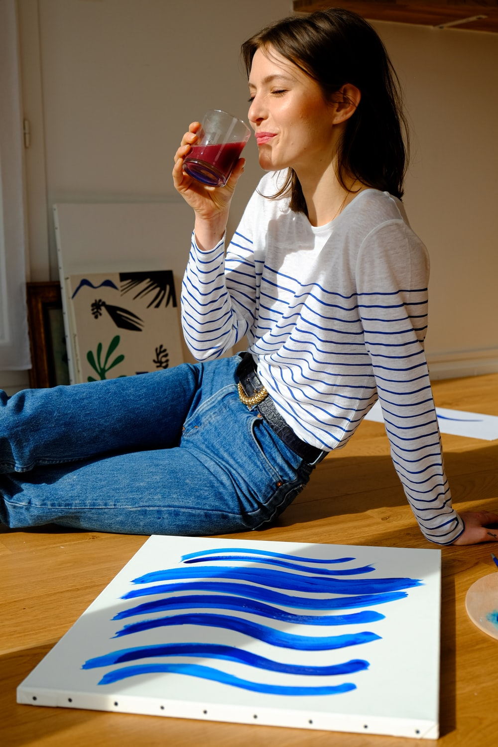 woman in white and black striped long sleeve shirt and blue denim jeans sitting on brown