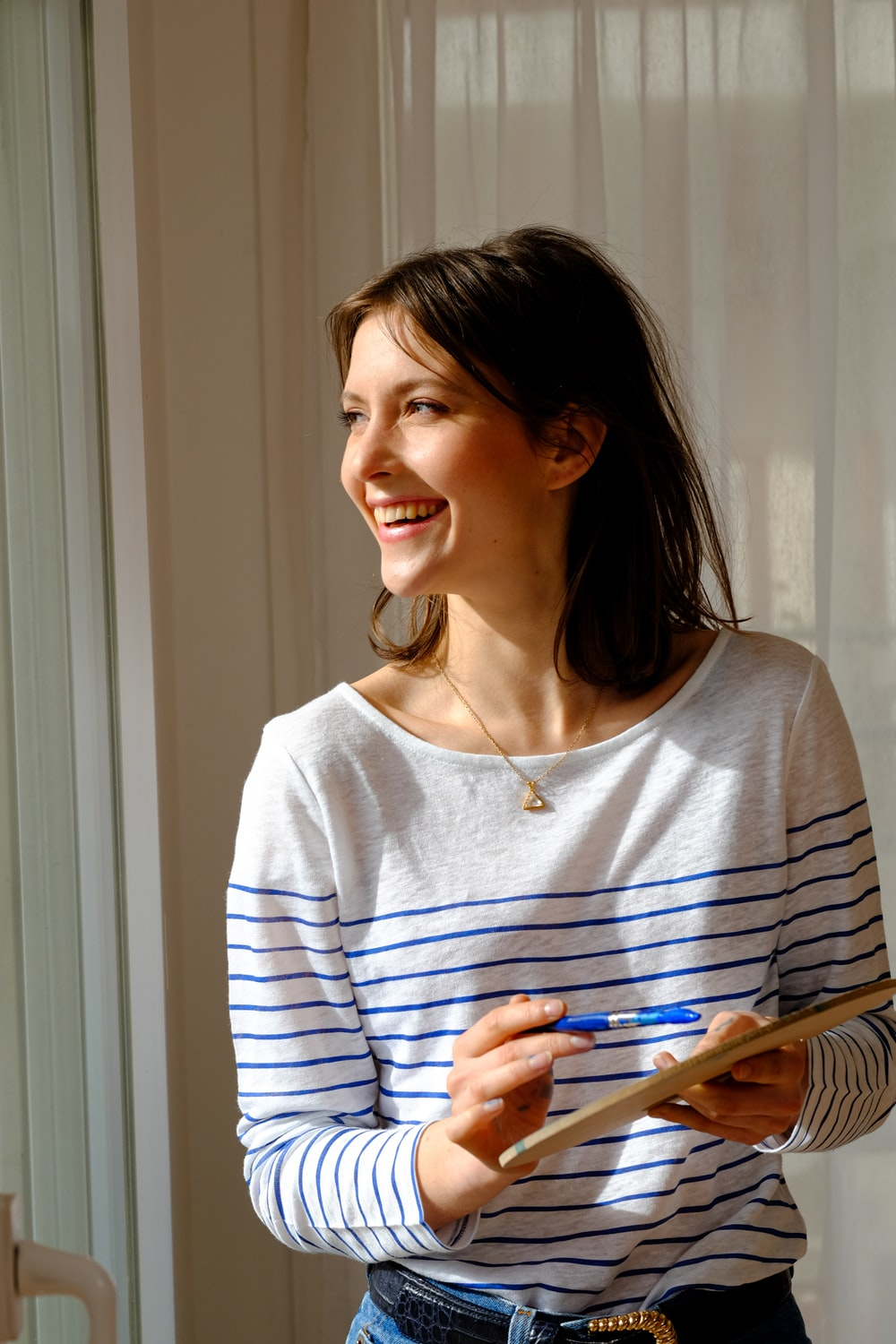 woman in gray and white striped long sleeve shirt smiling
