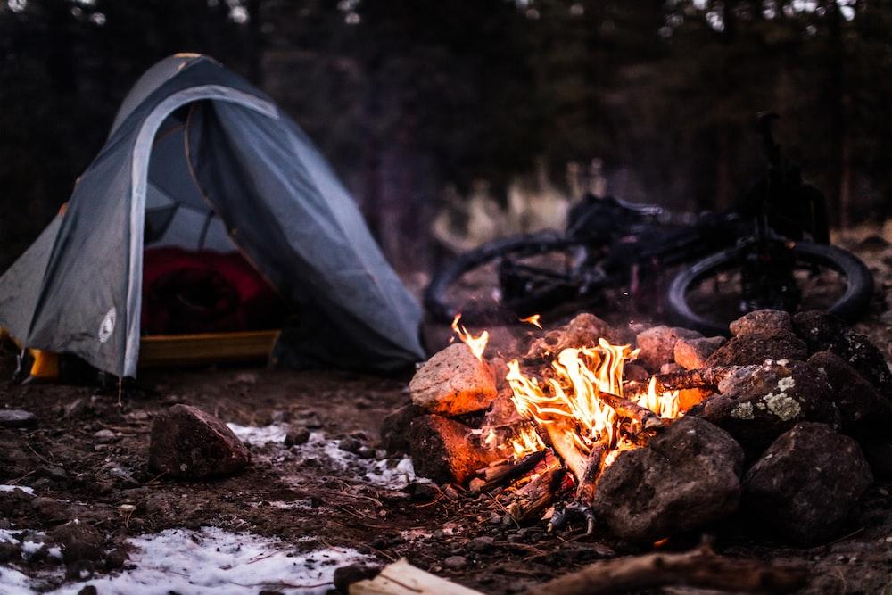 bonfire near gray tent during daytime